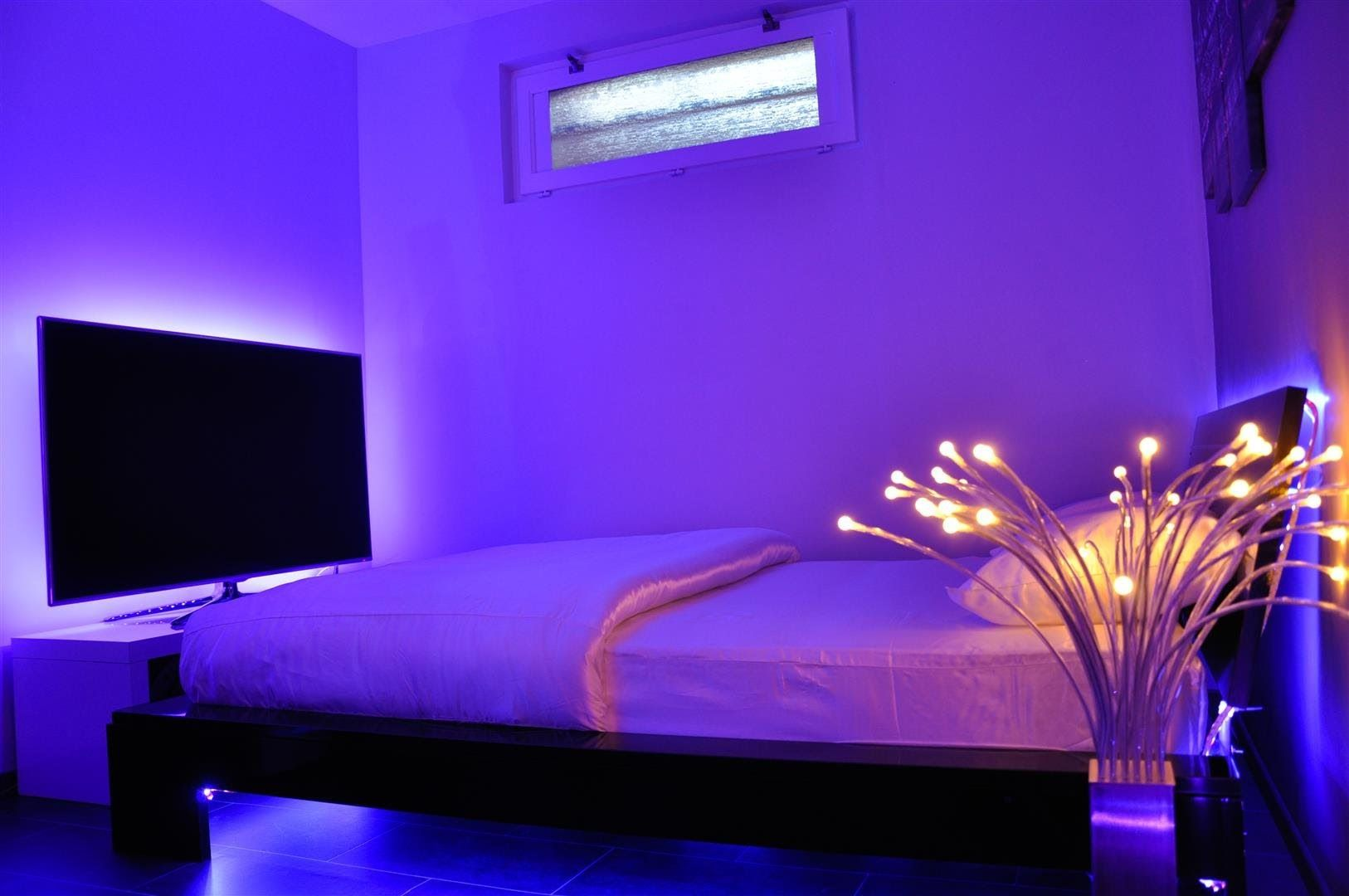 bedroom with a tv the has strip lighting illuminating it from behind