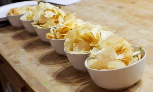 A row of crisps in bowls.