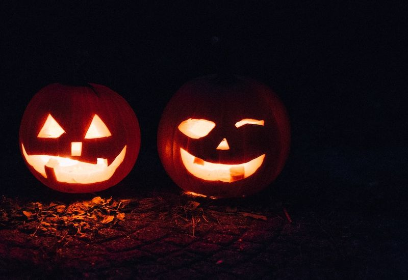 Two Jack-o'-Lanterns lit up in the dark.