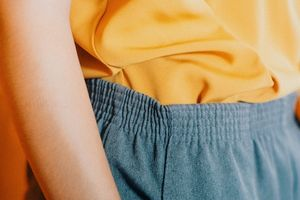 A close up of an orange women's blouse tucked into trousers.