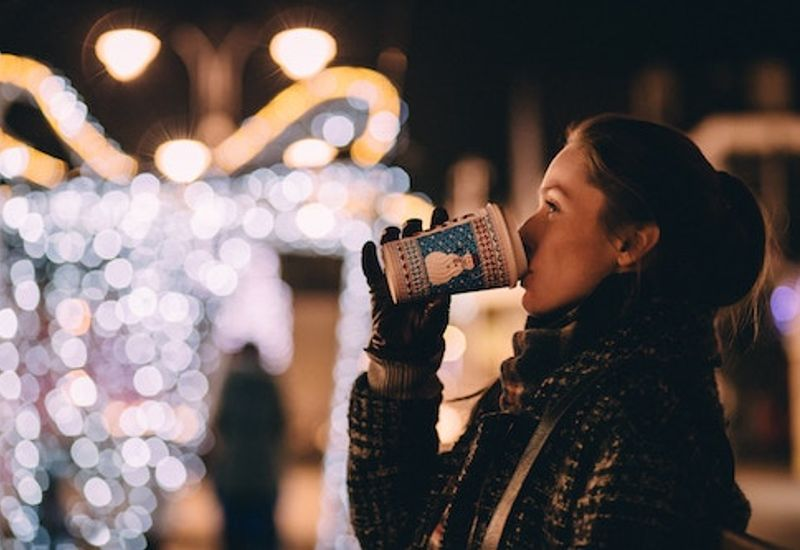 Woman drinking a hot drink next to outdoors Christmas decorations.