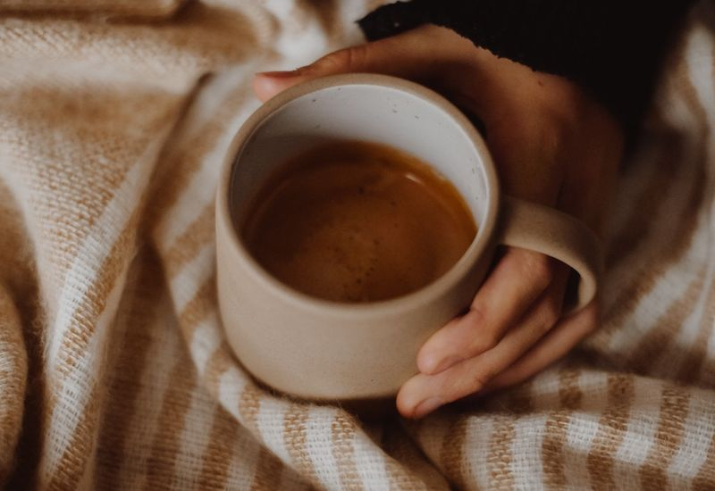 Woman holding coffee in bed.