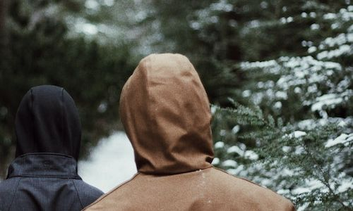 A shot of a person with a hooded brown coat walking through a snowy forest.