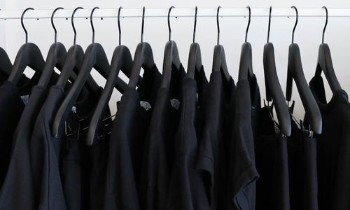 A clothing rail with a range of black tops hanging off.