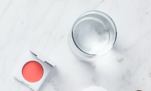 Cosmetics on a white marble surface.