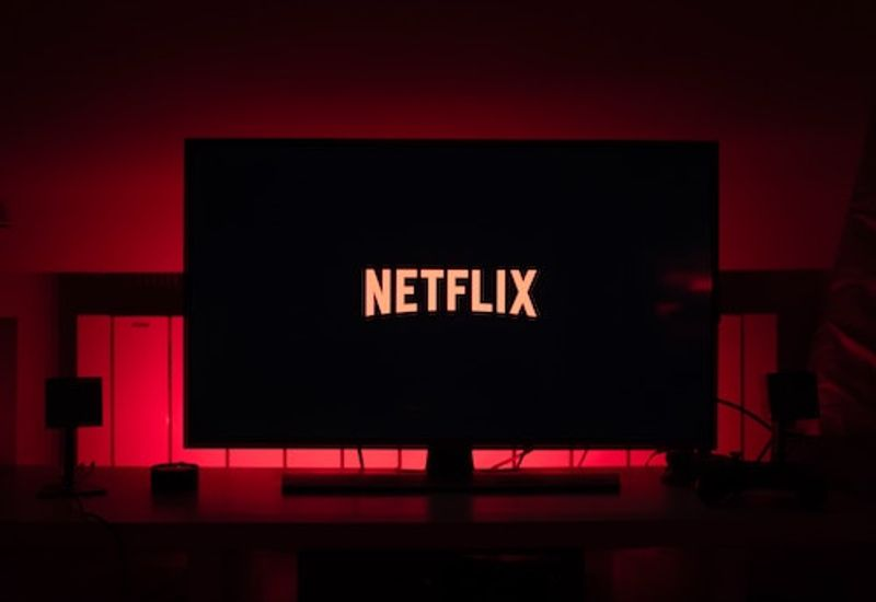 A TV displaying Netflix in a dark room.